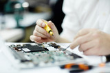 Closeup shot of unrecognizable man assembling circuit board using screwdriver and different tools on table in workshop
