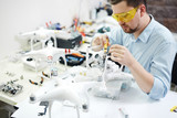 Portrait of modern man setting up new high tech drones and attaching cameras in electronic workshop