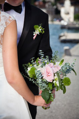 The bride and groom hug near sea, hold wedding bouquet from pink