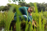 Beautiful emotional girl sits on a lake among the grass and wate