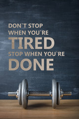 metal barbell on dark gray background and motivation text