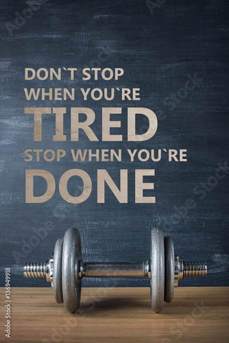 Poster metal barbell on dark gray background and motivation text