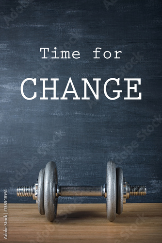 Fototapeta metal barbell on dark gray background and motivation text time for change