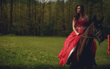 Beautiful young woman dressed medieval dress rides brown horse