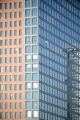 Moderne Hochhausfassade / Die moderne Fassade eines Hochhauses mit Spiegelungen in den Fenstern.