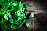 Fresh green baby spinach leaves  in a bowl on a rustic wooden ta