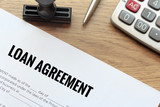 Loan agreement document with rubber stamp and calculator on wood