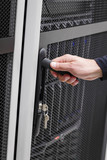 IT engineer opens door to server rack in datacenter