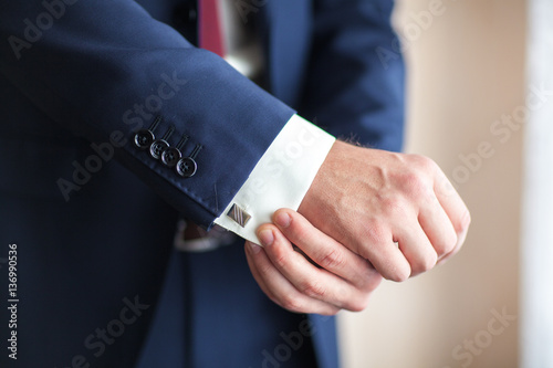 Poster Closeup of a businessman with hands closing elegant blue suit jacket adjusts his