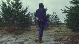 Girl walking between the trees, across the winter field. Super slow motion footage.