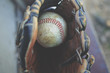 Baseball glove holding old rough ball, ready for a game of catch.