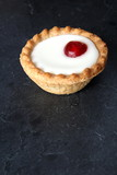 Cherry bakewell tart on dark background