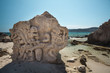 Sculpture carved in the rock at the beach Salinas in Ibiza