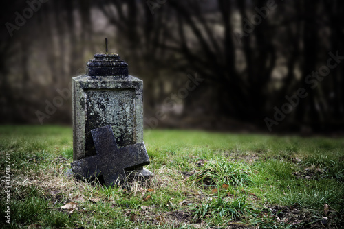 Broken stone cross, weathered gravestone on an old abandoned cementery, hallowee Poster