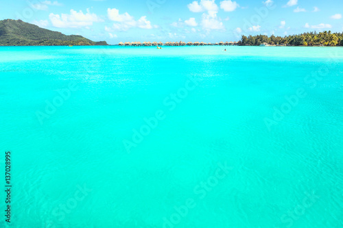 Stunning view of blue turquoise lagoon and far bungalows on back