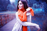 young girl in an orange scarf on a walk in the park