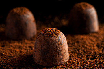 Three chocolate sweets with ground coffee, closeup shot
