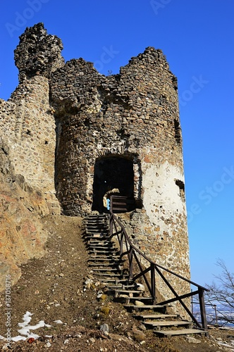 Poster Ruin of round gothic tower with wooden stairs on castle Reviste, Slovakia