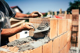 Industrial construction worker using spatula and trowel for building walls with bricks and mortar - 137063168