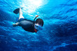 young man snorkeling down into the deep blue ocean sea background