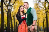 Mann und Frau mit bayrischer Tracht in vertrauter Pose, stehend vor herbstlicher Allee - 137077325