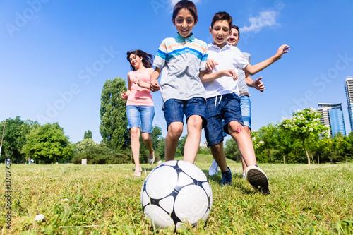 Familie beim Fußballspielen im Park im Sommer