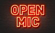 Open mic neon sign on brick wall background.