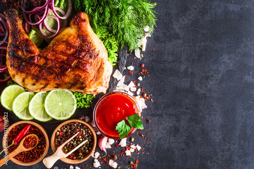 Roasted chicken legs with vegetables on dark background - 137095522