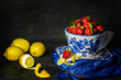 still life with fresh strawberries placed in porcelain bowl with lemons and blue scarf on dark background..