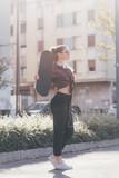 Young blonde caucasian skater woman posing outdoor in back light holding skateboard - sportive, skater, rebel concept