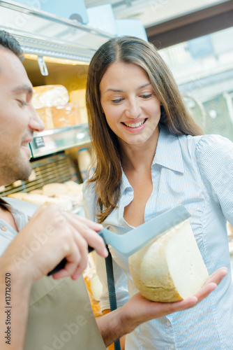 Poster Shop assistant determining with customer where to slice cheese