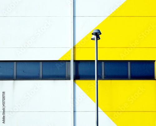 Yellow and white minimalist facade of a modern building with a street lamp © luca pb