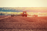 Tractor plowing farm field in preparation for spring planting - 137130386