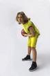 Young boy with long blond hair wearing a green jersey in a squatting position holding a basketball