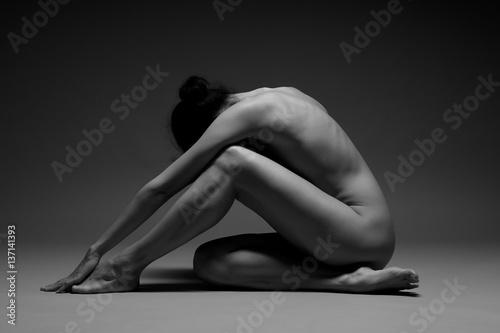 beautiful nude woman practicing yoga