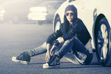 Young fashion woman in sunglasses sitting next to her car