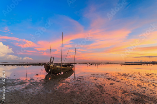 Wrecked fishing boat at sea with sunset