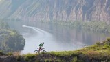 The sporty woman riding bicycle in mountain nature landscape.