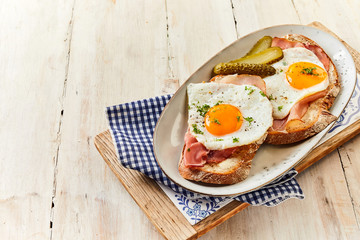Eggs cooked sunny side up with ham on bread