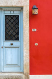 old blue wooden door in composition with a vivid red painted wall. A beautiful combination of colours in a building located in the traditional colorful and awarded village of Crete, Archanes.