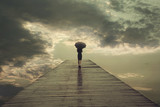 Fototapety mysterious woman with umbrella crosses a bridge to the threatening sky