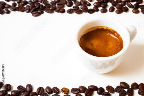 cup of fresh espresso coffee, coffee beans on top and bottom, empty space on left