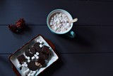 Hot chocolate in a blue mug, marshmellows, and chocolate cookies on a dark blue wooden tabletop
