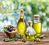 Olive oil and berries are on the wooden table under the olive tree. - 137199922