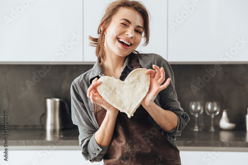 Cheerful lady holding the dough heart.