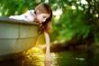 Cute little girl having fun in a boat by a river