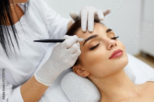 Leinwandbild Motiv Beautician Doing Permanent Eyebrows Makeup Tattoo On Woman Face