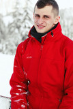 Smiling young man in red ski jacket poses in white forest