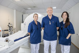 Confident Medical Team Smiling By MRI Machine