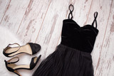 Black evening dress and shoes on a wooden background. Fashion concept. Top view, space for text - 137236381